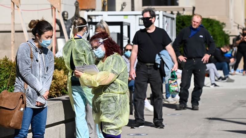 A health-care official takes information as people line up at a COVID assessment centre during the COVID-19 pandemic in Toronto on Friday, September 18, 2020. Ontario is reporting 401 new cases of COVID-19 today, a daily increase not seen since early June. THE CANADIAN PRESS/Nathan Denette