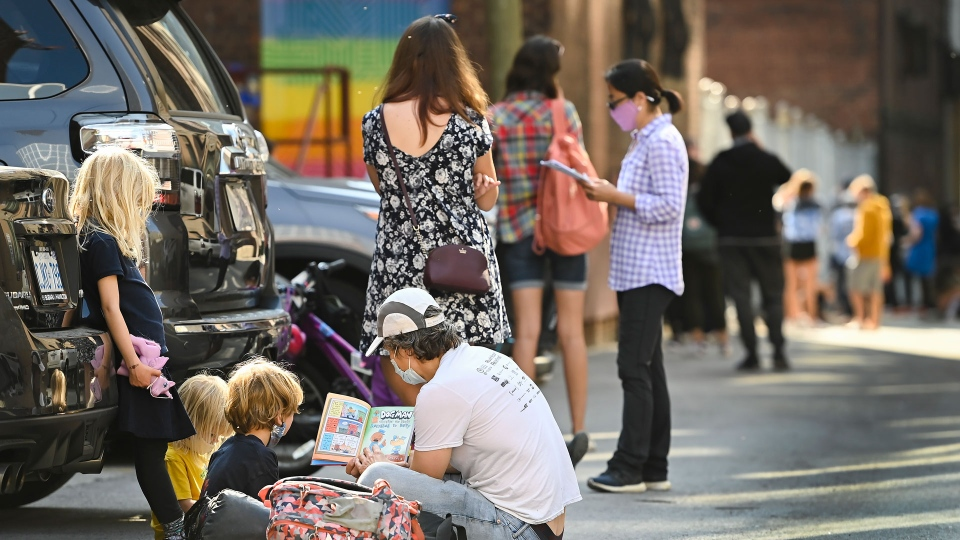 A family reads a book as they sit in an alleyway for hours at a COVID assessment centre at St. Michael's Hospital during the COVID-19 pandemic in Toronto on Monday, September 28, 2020. THE CANADIAN PRESS/Nathan Denette