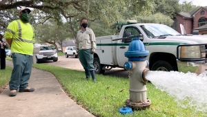 City workers Kristina Watson, right, and Lennie Miner, a maintenance foreman monitor Monday, Sept. 28, 2020, test water flowing out of a hydrant in Lake Jackson, Texas. (AP Photo/Jim Mone)
