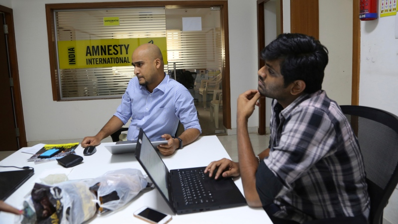 In this Tuesday, Feb. 5, 2019, file photo, Amnesty International India employees work at their headquarters in Bangalore, India. (AP Photo/Aijaz Rahi, File)