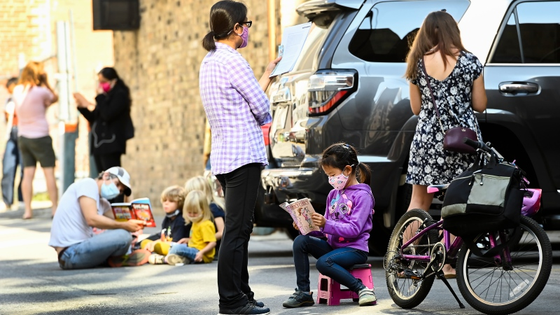 Families read books as they sit in an alleyway for hours at a COVID assessment centre at St. Michael's Hospital during the COVID-19 pandemic in Toronto on Monday, September 28, 2020. THE CANADIAN PRESS/Nathan Denette