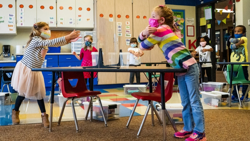 "In this Sept. 10, 2020, file photo, Kindergarten students practice air hugs while watching a video on how to ""greet from 6 feet"" during class at Wildwood Elementary in Stillwater, Minn. (Evan Frost /Minnesota Public Radio via AP, File)"