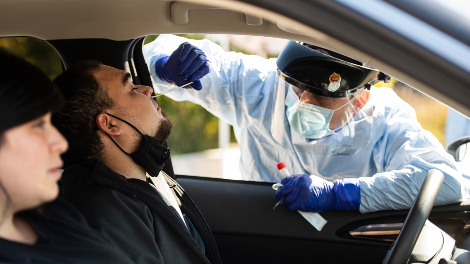 A paramedic administers a nasal swab at a drive through, pop-up COVID-19 test centre outside the Canadian Tire Centre in Ottawa, Sunday, Sept. 20, 2020. THE CANADIAN PRESS/Justin Tang