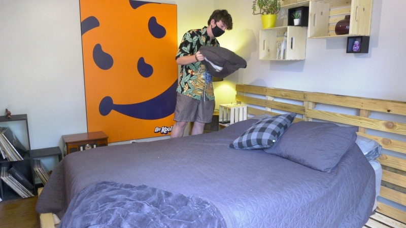 Erick Cole fixing the sheets on the bed he built himself. (Dave Charbonneau / CTV News Ottawa)