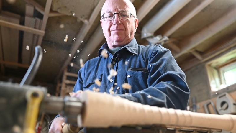 Bill Ryan turns a baseball bat on the lathe in his basement workshop. (Joel Haslam / CTV News Ottawa)