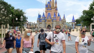 In this Saturday, July 11, 2020, file photo, guests wear masks as required to attend the official reopening day of the Magic Kingdom at Walt Disney World in Lake Buena Vista, Fla. (Joe Burbank/Orlando Sentinel via AP, File)