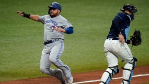 Toronto Blue Jays' Rowdy Tellez, left, scores behind Tampa Bay Rays catcher Mike Zunino on a sacrifice fly by Bo Bichette during the eighth inning of Game 1 of a wild card series playoff baseball game Tuesday, Sept. 29, 2020, in St. Petersburg, Fla. (AP Photo/Chris O'Meara)