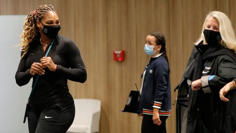 Serena Williams, left, leaves after a press conference in which she announced her withdrawal from the French Open tennis tournament, on Sept. 30, 2020. (Christophe Ena / AP)