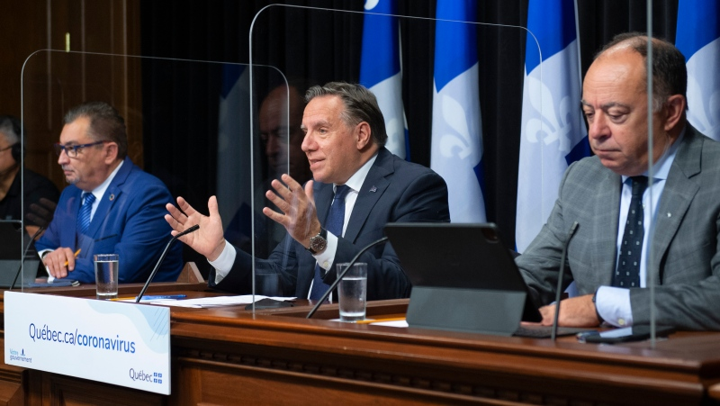 Quebec Premier Francois Legault, centre, speaks during a news conference on the COVID-19 pandemic, Tuesday, September 29, 2020 at the legislature in Quebec City. Legault is flanked by Horacio Arruda, Quebec director of National Public Health, left, and Quebec Health Minister Christian Dube. A plexiglass screen was installed to have social distancing. THE CANADIAN PRESS/Jacques Boissinot