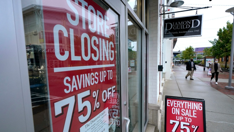 Pedestrians walk past a business storefront with store closing and sale signs in Dedham, Mass., on Sept. 2, 2020. (Steven Senne / AP)