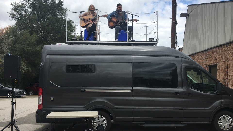 Eric Ethridge and Kalsey Kulyk perform on top of their van in London, Ont. on Wednesday, Sept. 30, 2020. (Brent Lale / CTV News)