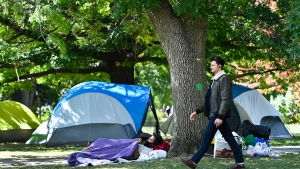A person walks past a homeless man as he rests beside tents set up in Trinity Bellwoods Park during the COVID-19 pandemic in Toronto on Monday, September 21, 2020. THE CANADIAN PRESS/Nathan Denette
