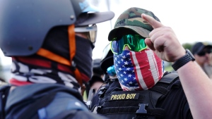 "In this Sept. 26, 2020 file photo, a right-wing demonstrator gestures toward a counter protester as members of the Proud Boys and other right-wing demonstrators rally in Portland, Ore. President Donald Trump didn't condemn white supremacist groups and their role in violence in some American cities this summer. Instead, he said the violence is a ""left-wing"" problem and he told one far-right extremist group to ""stand back and stand by."" His comments Tuesday night were in response to debate moderator Chris Wallace asking if he would condemn white supremacists and militia groups. Trump's exchange with Democrat Joe Biden left the extremist group Proud Boys celebrating what some of its members saw as tacit approval. (AP Photo/John Locher, File)"