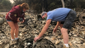 "Kevin Conant and his wife, Nikki, sift through debris of their burnt home and business ""Conants Wine Barrel Creations,"" after the Glass/Shady fire completely engulfed it, Wednesday, Sept. 30, 2020, in Santa Rosa, Calif. (AP Photo/Haven Daley)"