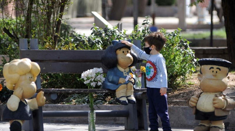 A child touches a statue depicting Mafalda, the comic strip character created by Argentinian cartoonist Joaquin Salvador Lavado, known as Quino, who died on Wednesday