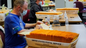 Workers seal envelopes of mail-in ballots at the Douglas County Election Commission's office in Omaha, Neb., Monday, Sept. 28, 2020. (AP Photo/Nati Harnik)