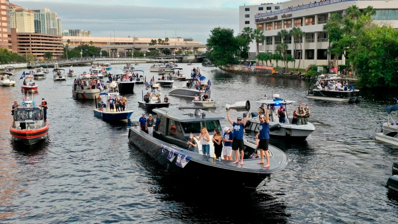 Members of the Tampa Bay Lightning make their way down the Hillsborough River as they are greeted by fans during the NHL hockey Stanley Cup champions' boat parade, Wednesday, Sept. 30, 2020, in Tampa, Fla. (Luis Santana/Tampa Bay Times via AP)
