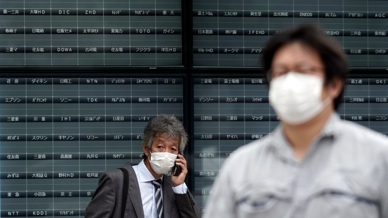A man stands in front of a blank electronic stock board supposedly showing Japan's Nikkei 225 index at a securities firm in Tokyo Thursday, Oct. 1, 2020. (AP Photo/Eugene Hoshiko)