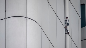 """French urban climber Alain Robert, well known as """"Spiderman"""", climbs up the Deutsche Bahn high-rise in central Frankfurt, Germany, Thursday, Oct. 1, 2020. Robert was wearing a silver suit and cowboy boots. (AP Photo/Michael Probst)"""