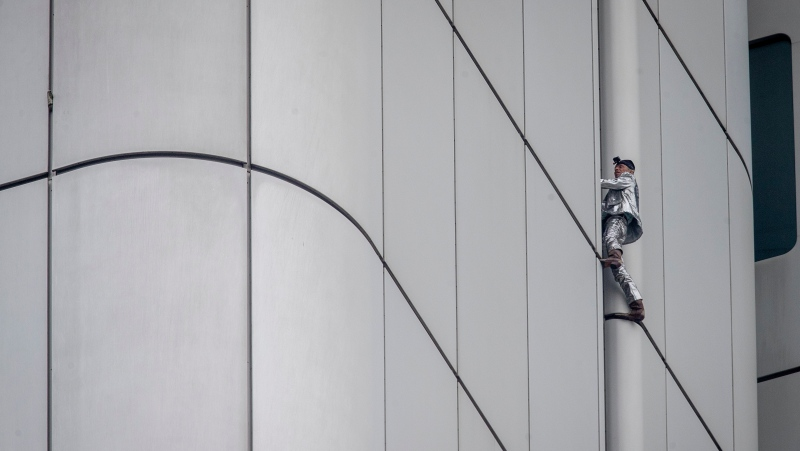 "French urban climber Alain Robert, well known as ""Spiderman"", climbs up the Deutsche Bahn high-rise in central Frankfurt, Germany, Thursday, Oct. 1, 2020. Robert was wearing a silver suit and cowboy boots. (AP Photo/Michael Probst)"