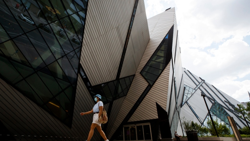 A person wearing a mask walks by the Royal Ontario Museum in Toronto, on Friday, June 26, 2020. THE CANADIAN PRESS/Cole Burston