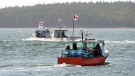 Members of the Potlotek First Nation, head out into St. Peters Bay from the wharf in St. Peter's, N.S. as they participate in a self-regulated commercial lobster fishery on Thursday, Oct. 1, 2020, which is Treaty Day.  (THE CANADIAN PRESS /Andrew Vaughan)