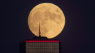 The nearly full moon rises, with an office building in the foreground, Wednesday, Sept. 30, 2020, in downtown Kansas City, Mo. (AP Photo/Charlie Riedel)