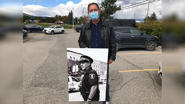 Const. Bruce Lemcke holds a photo of his early days working downtown Orangeville, Ont., with the municipal police force. Oct. 1, 2020. (Rob Cooper/CTV News)