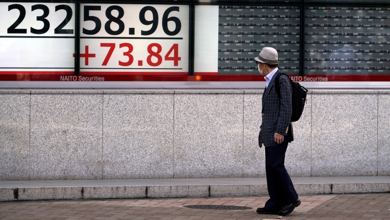 A man looks at an electronic stock board showing Japan's Nikkei 225 index at a securities firm Friday, Oct. 2, 2020, in Tokyo. (AP Photo/Eugene Hoshiko)