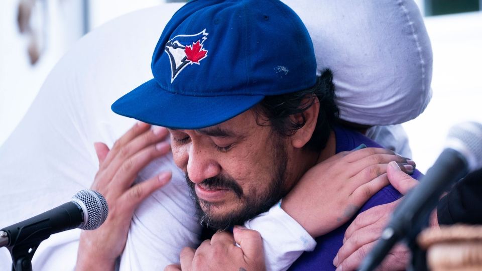 Carol Dube, husband of Joyce Echaquan, is hugged by one of his sons Dayvon as he breaks down while reading a statement in Joliette, Que. on Friday, October 2, 2020. Echaquan, an indigenous woman, was subjected to insults as she lay dying in a local hospital. THE CANADIAN PRESS/Paul Chiasson
