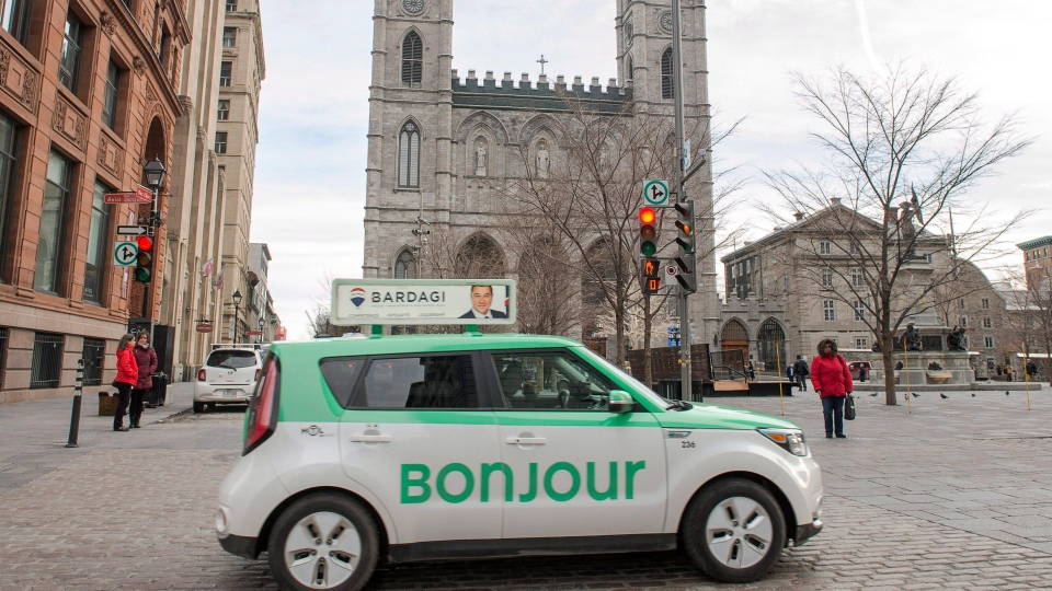 A taxi with Bonjour on the side drives past the Notre-Dame Basilica in Montreal on Thursday, November 30, 2017. The National Assembly is formally asking Quebec's merchants to