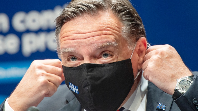 Quebec Premier Francois Legault removes his face mask as he arrives for the COVID-19 media briefing, Friday, October 2, 2020 in Montreal.THE CANADIAN PRESS/Ryan Remiorz