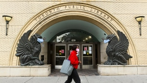 A woman walks past a Toronto Public Library where masks cover the faces of statues during the COVID-19 pandemic in Toronto on Friday, October 2, 2020. THE CANADIAN PRESS/Nathan Denette