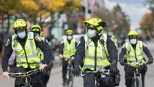 Police wear face masks as they patrol Sainte-Catherine Street in Montreal, Saturday, October 3, 2020, as the COVID-19 pandemic continues in Canada and around the world. THE CANADIAN PRESS/Graham Hughes