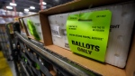 A cart holding vote-by-mail ballots is seen before being loaded into a truck for transport to a local U.S. Postal Service office, Thursday, Oct. 1, 2020, at the Miami-Dade County Elections Department in Doral, Fla. (AP Photo/Wilfredo Lee)