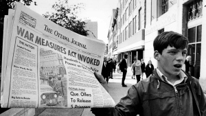 A newsboy holds up a newspaper with a banner headline reporting the invoking of the War Measures Act Oct 16, the first time Canada had invoked the act in peacetime. The act was put into effect following the kidnapping of British diplomat James Cross and Quebec labour minister Pierre Laporte by the FLQ. (CP PHOTO/Peter Bregg) 1970
