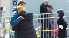A couple hug as they wait in line at a COVID-19 testing clinic Tuesday, October 6, 2020 in Montreal. Quebec reported a record 1,364 new cases of the virus.THE CANADIAN PRESS/Ryan Remiorz