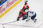 Winnipeg Jets' Dylan DeMelo (12) and Calgary Flames' Matthew Tkachuk (19) battle for the puck during third period NHL qualifying round game action in Edmonton, on Monday August 3, 2020. THE CANADIAN PRESS/Jason Franson