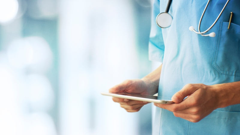 A nurse holds a tablet in this stock image from Shutterstock.
