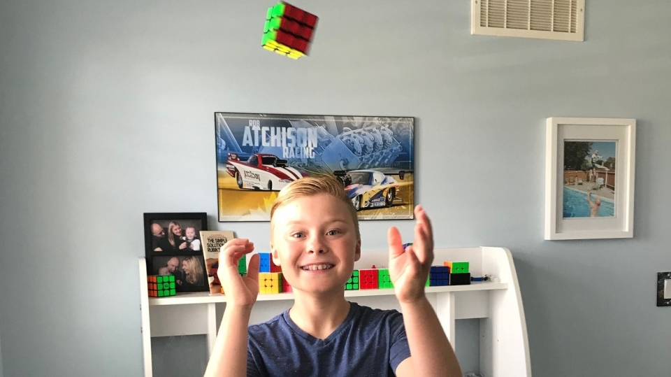Wyatt Atchison tossing a Rubik's cub in the air