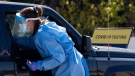 A paramedic reaches into a vehicle window to administer a nasal swab test at a drive through, pop-up COVID-19 test centre outside the Canadian Tire Centre, home of the NHL's Ottawa Senators, in Ottawa, Sunday, Sept. 20, 2020. THE CANADIAN PRESS/Justin Tang