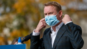 Minister of Health Tyler Shandro, removes his made-in-Calgary mask while announcing a new agreement between Alberta Health Services and a local manufacturer to produce medical equipment, in Calgary, Alta., Wednesday, Oct. 7, 2020.THE CANADIAN PRESS/Jeff McIntosh