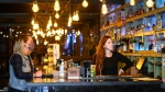 Bartender Victoria Colombe, right, and manager Amanda Godinho, left, watch the news on a television while working at Door Fifty Five bar and restaurant during the COVID-19 pandemic in the Port Credit neighbourhood of Mississauga, Ont., Friday, Oct. 9, 2020. THE CANADIAN PRESS/Nathan Denette