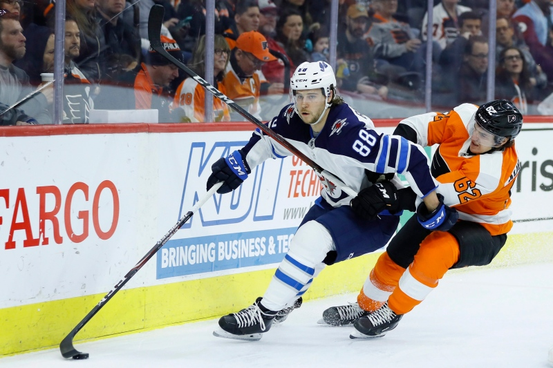 Winnipeg Jets' Nathan Beaulieu (88) tries to keep Philadelphia Flyers' Nicolas Aube-Kubel (62) away from the puck during the second period of an NHL hockey game, Saturday, Feb. 22, 2020, in Philadelphia. (AP Photo/Matt Slocum)