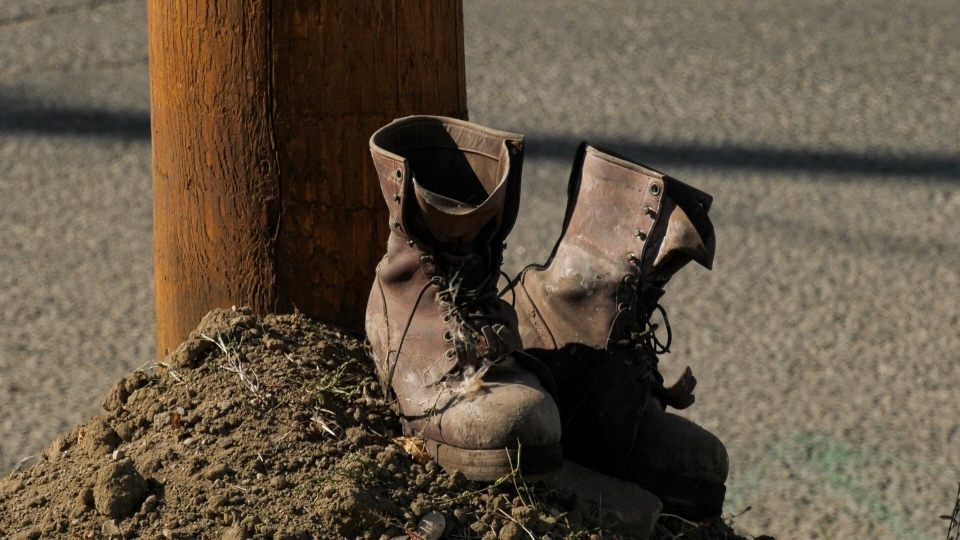 A pair of work boots were placed at the base of a power line in Weyburn, where two SaskPower workers died on Thursday. (Marc Smith / CTV News Regina)