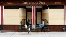 People walk past the boarded up windows of a pub in Ottawa's Byward Market that remains closed due to the COVID-19 pandemic, on Friday, April 10, 2020. THE CANADIAN PRESS/Justin Tang