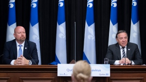 Quebec Premier Francois Legault, right speaks as Quebec Indigenous Affairs Minister Ian Lafreniere, left, looks on, at a news conference after he was sworn in, Friday, October 9, 2020 at the legislature in Quebec City. Lafreniere replaces Sylvie D'Amour. THE CANADIAN PRESS/Jacques Boissinot