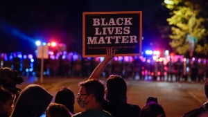 Protesters and police line up Friday, Oct. 9, 2020, in Wauwatosa, Wis. On Wednesday, District Attorney John Chisholm refused to issue charges against Wauwatosa Police Officer Joseph Mensah for the Feb. 2 fatal shooting of 17-year-old Alvin Cole at Mayfair Mall. (AP Photo/Morry Gash)