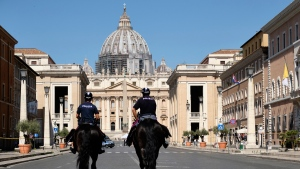 Horse mounted police officers patrol Via della Conciliazione, the street leading to St. Peter's Basilica at the Vatican, on Monday, June 29, 2020. (Mauro Scrobogna/LaPresse via AP)