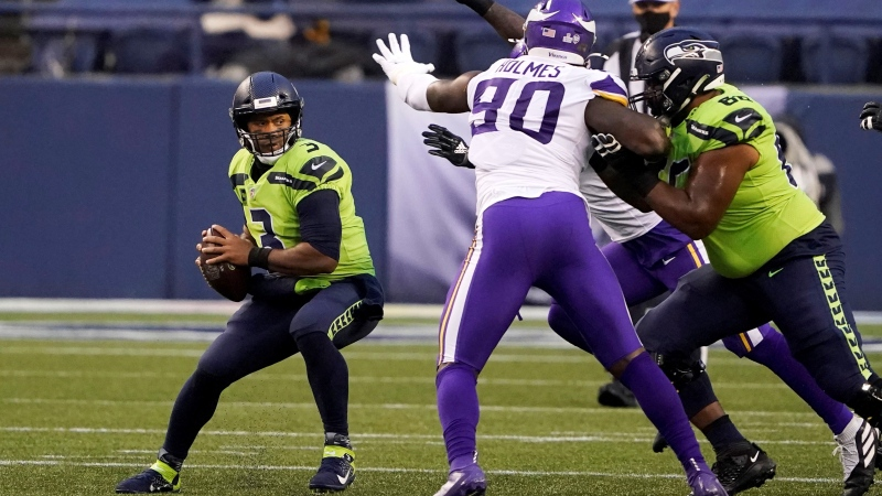 Seattle Seahawks quarterback Russell Wilson, left, looks for room to pass against pressure from the Minnesota Vikings during the first half of an NFL football game, Sunday, Oct. 11, 2020, in Seattle. (AP / Ted S. Warren)